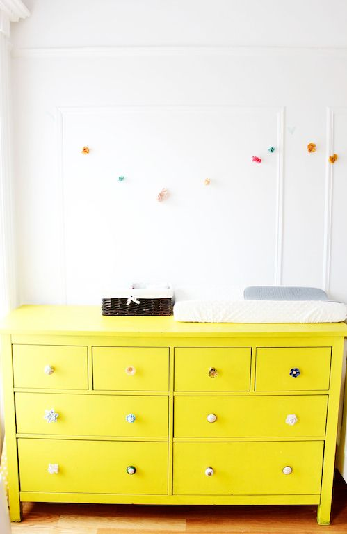 a neon yellow IKEA Hemnes dresser with all different knobs as a changing table for a colorful kids' space