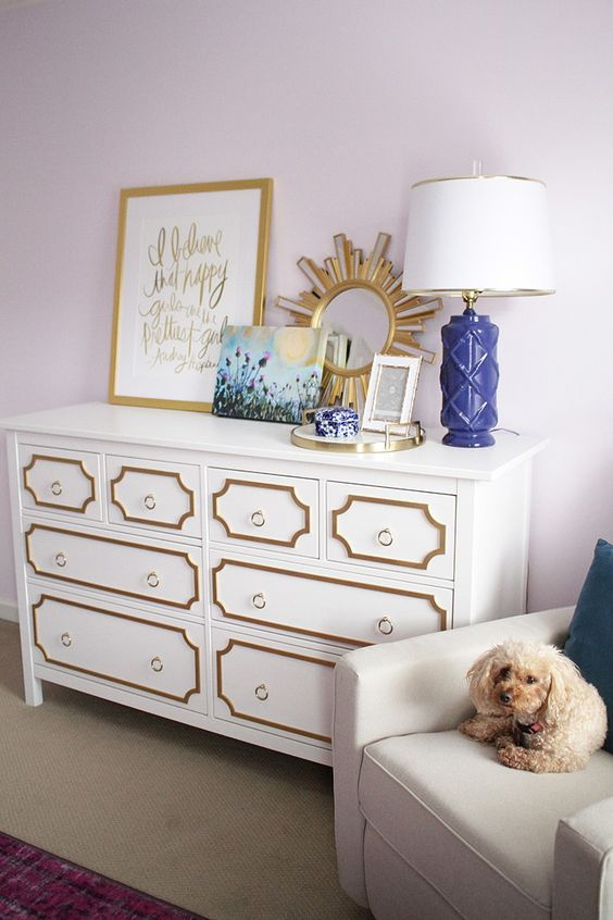 an elegant art deco Hemnes hack with gold framing and gold ring pulls for a chic look