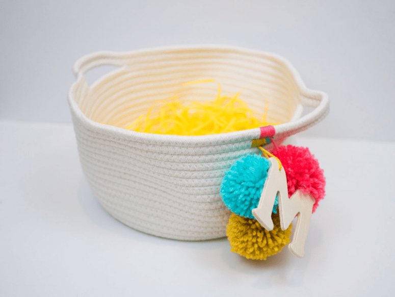 DIY rope basket with a monogram and colroful pompoms (via www.thehomesteady.com)
