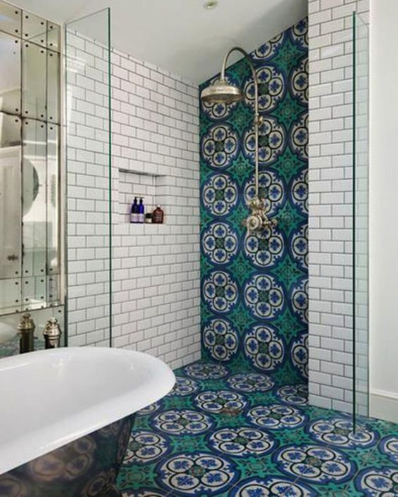 colorful Moroccan-inspired mosaic tiles in blue and green cover the wall and floor for a bright accent