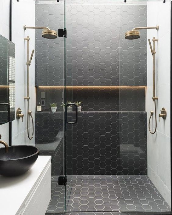 a contemporary bathroom with black hexagon tiles and white grout on the wall and floor