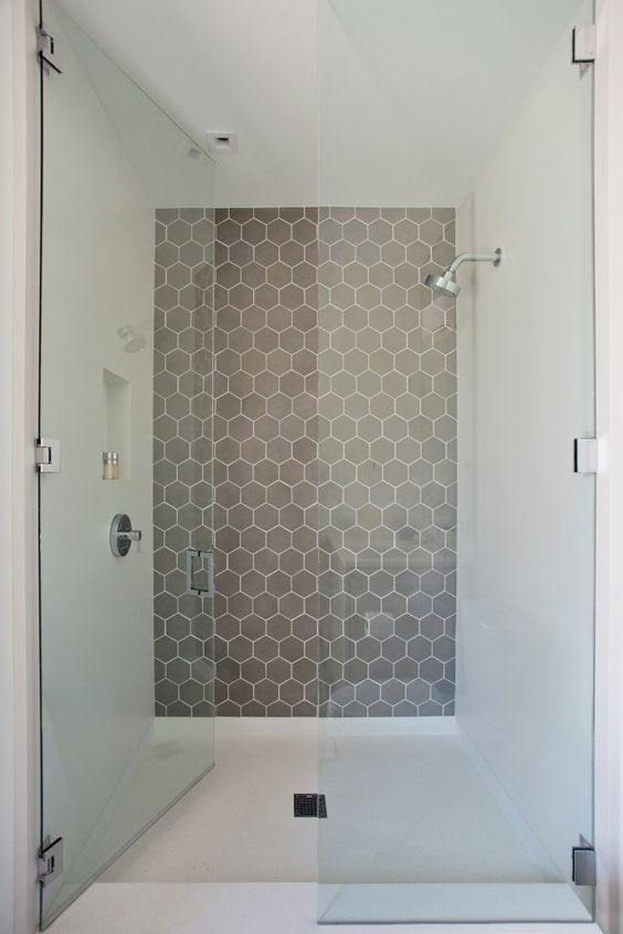 a minimalist bathroom with a shower statement wall done with grey hex tiles with white grout