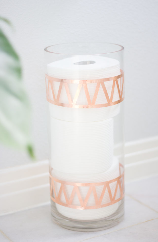 DIY toilet paper toll storage of a glass vase (via www.designimprovised.com)