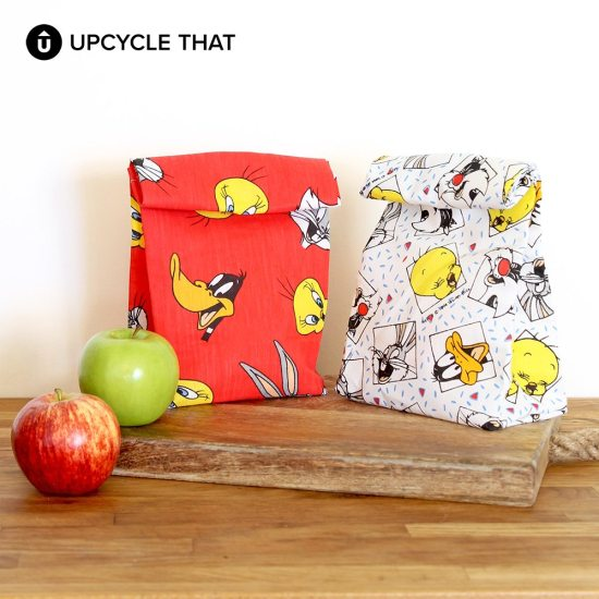 DIY cute scrap fabric lunch bags lined up with plastic bags (via www.upcyclethat.com)