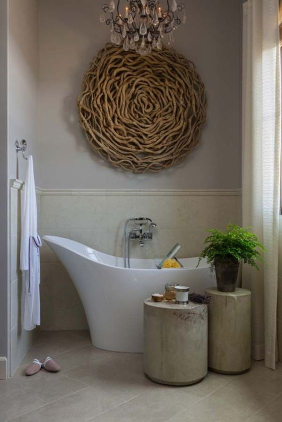 a chic bathroom spruced up with a driftwood artwork over the bathtub