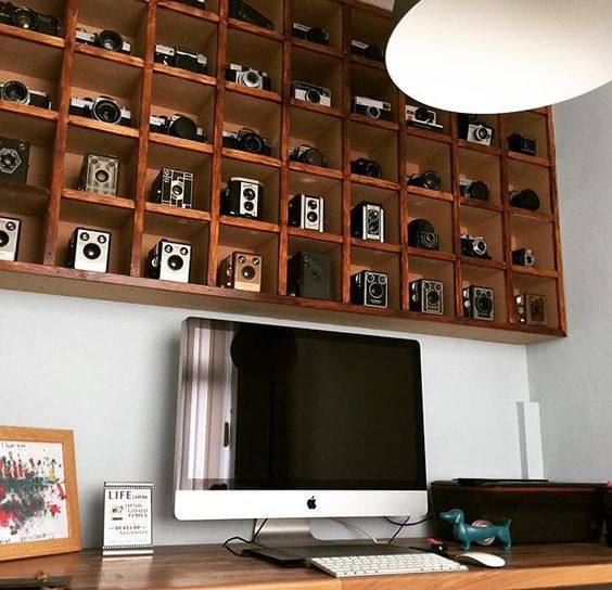an oversized box shelf display with a compartment for each camera is a bold decor feature