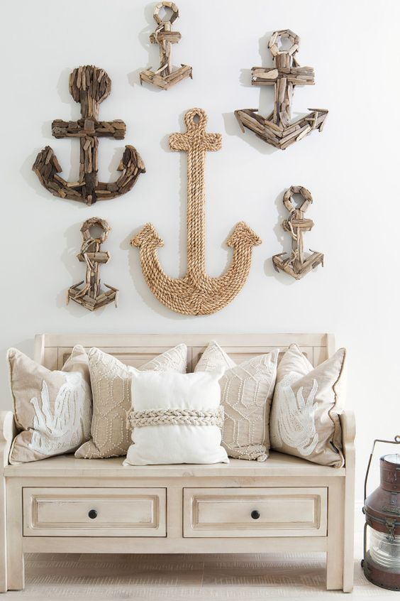 a coastal entryway with a creative art combo over the bench, the anchors are made of driftwood