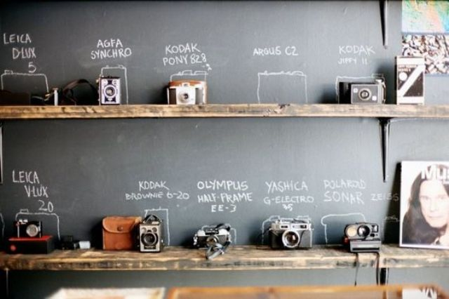 rustic wooden shelves and a chalkboard wall are great to display your cameras and sign them up