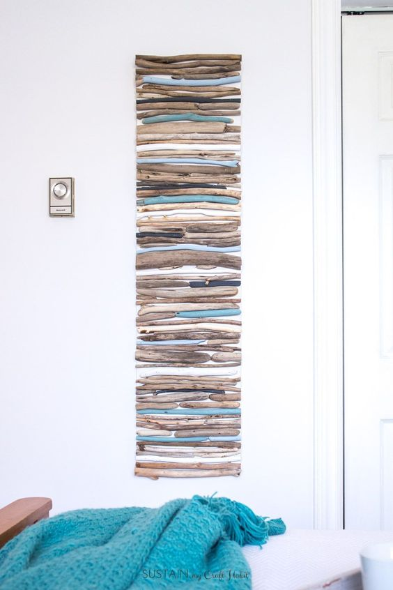 a gorgeous coastal artwork made of driftwood with painted parts looks chic and is easy to DIY