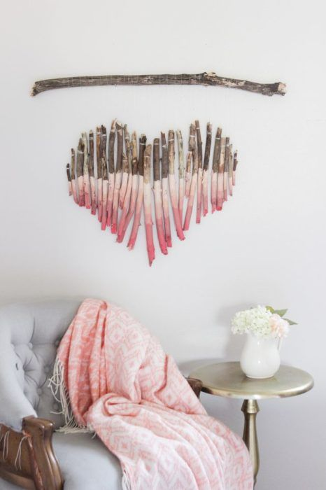a heart-shaped art piece of driftwood painted pink with an ombre effect