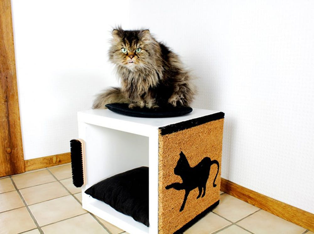 a scratching piece and cat bed in one made of IKEA Kallax unit
