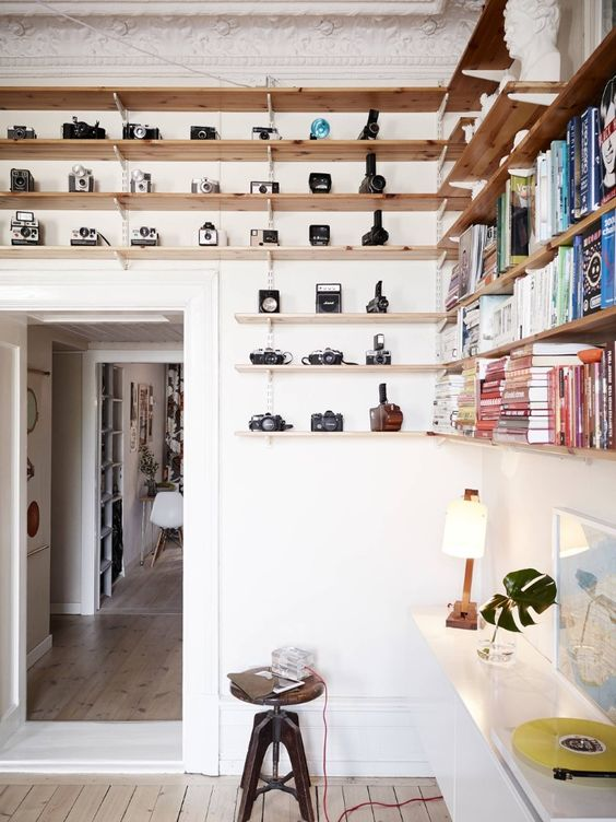 wooden shelves over the door is a great idea to use the awkward space and display cameras