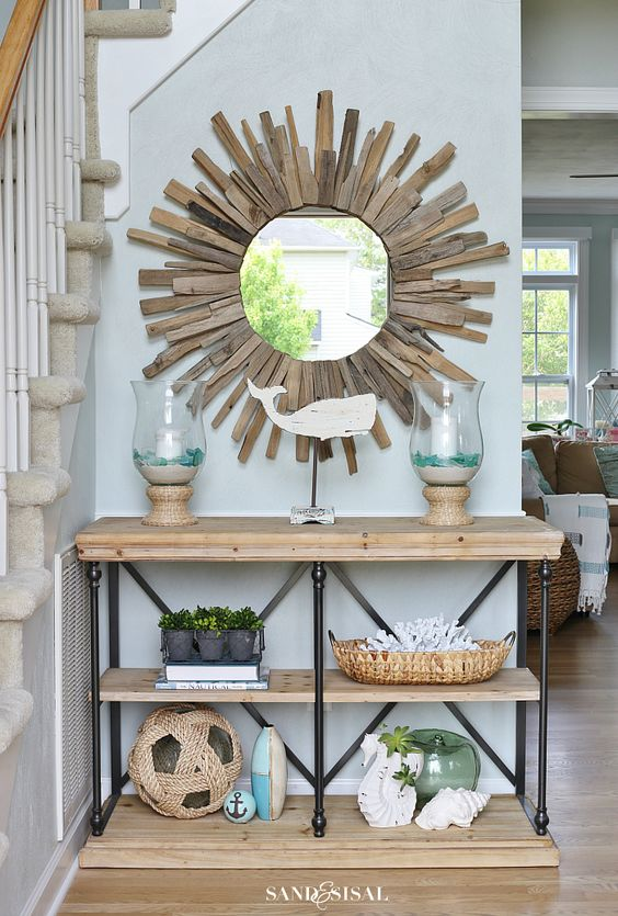 a coastal entryway with a starburst mirror clad with driftwood for a cool natural look