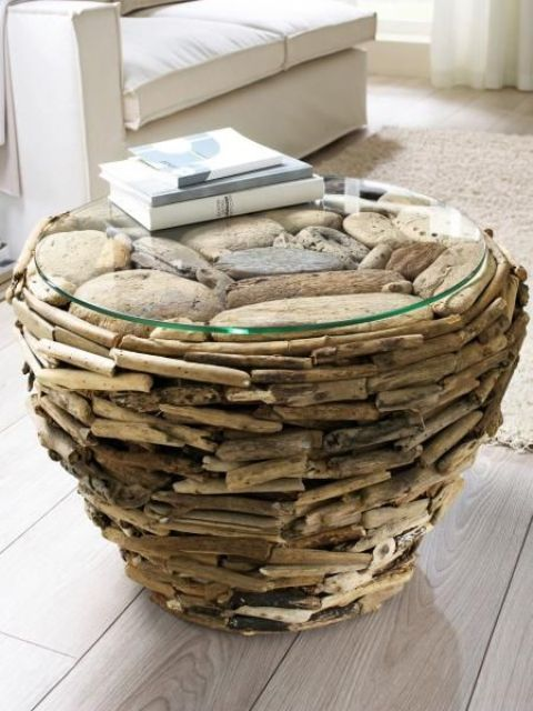 a coffee table built of driftwood and a glass tabletop is a unique touch of nature for the interior