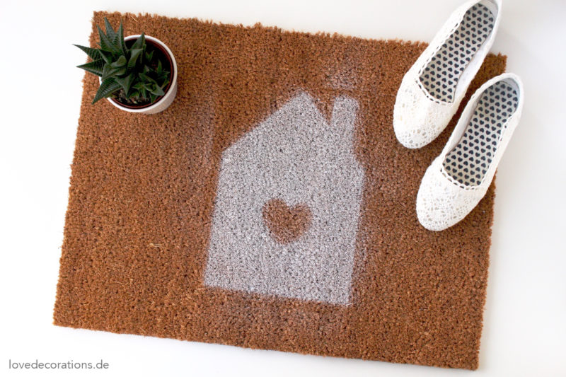 DIY neutral doormat with a white house with a heart