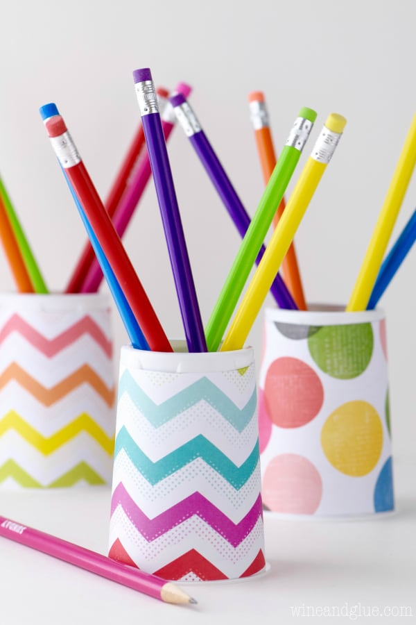 DIY yogurt cup pencil holder spruced up with colorful paper (via www.wineandglue.com)