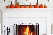 02 a rustic meets modern fall mantel with orange pumpkins and a wheat wreath on a mirror
