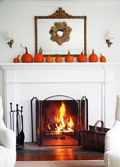 a rustic meets modern fall mantel with orange pumpkins and a wheat wreath on a mirror