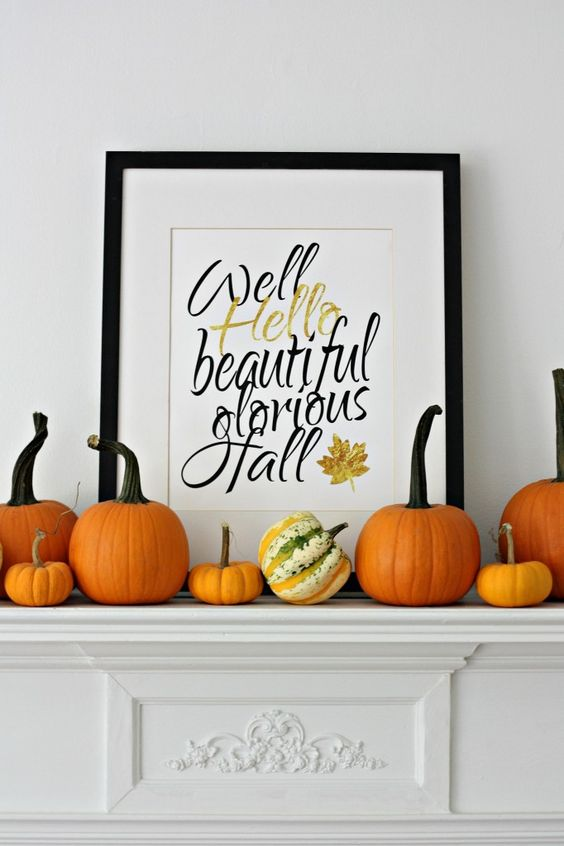 orange pumpkins on the mantel and a calligraphy fall sign in a frame for a simple look