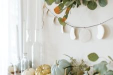 04 a modern fall mantel with neutral and pastel pumpkins, greenery, a greenery wreath and a banner
