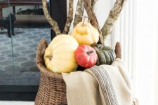 04 a modern tall basket filled with colorful pumpkins, branches and a blanket for coziness