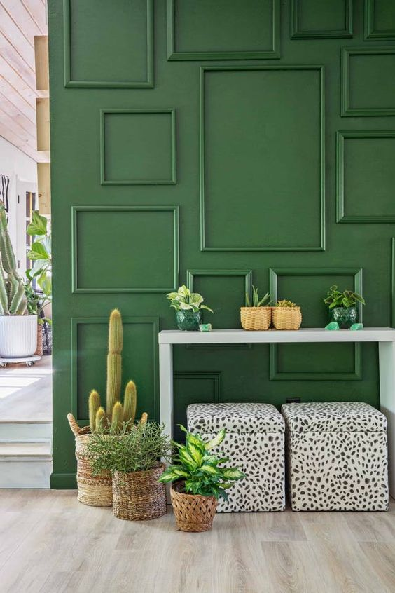 an accent wall with empty picture frames attached and painted emerald rings texture and color