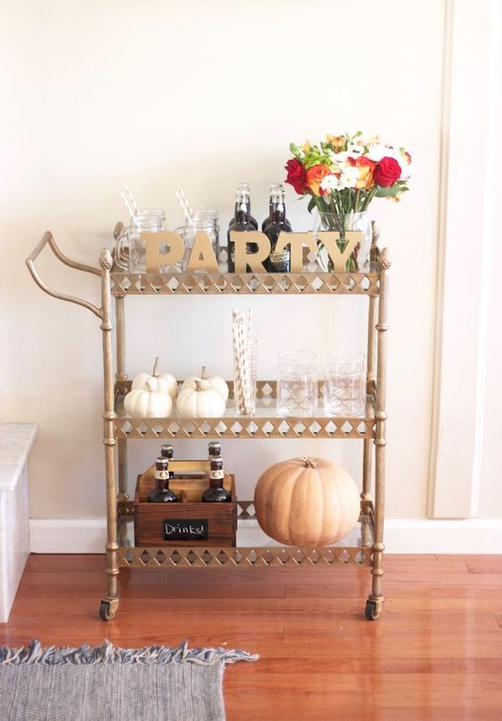 party hard this fall with a bar cart with a bright floral arrangement, gold letters and real pumpkins
