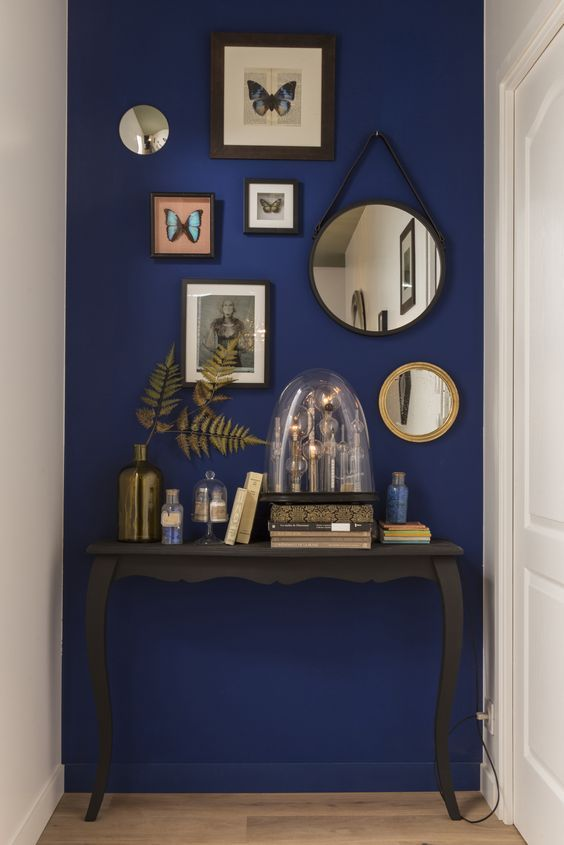an elegant vintage console is highlighted with a super bold blue accent wall