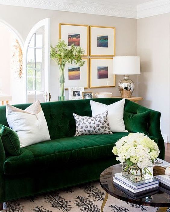 a cozy and bold emerald velvet sofa refreshed with white pillows