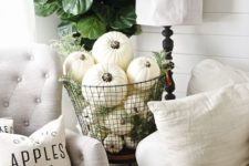 06 a metal wire basket fulled with white pumpkins and greenery for a vintage-inspired space