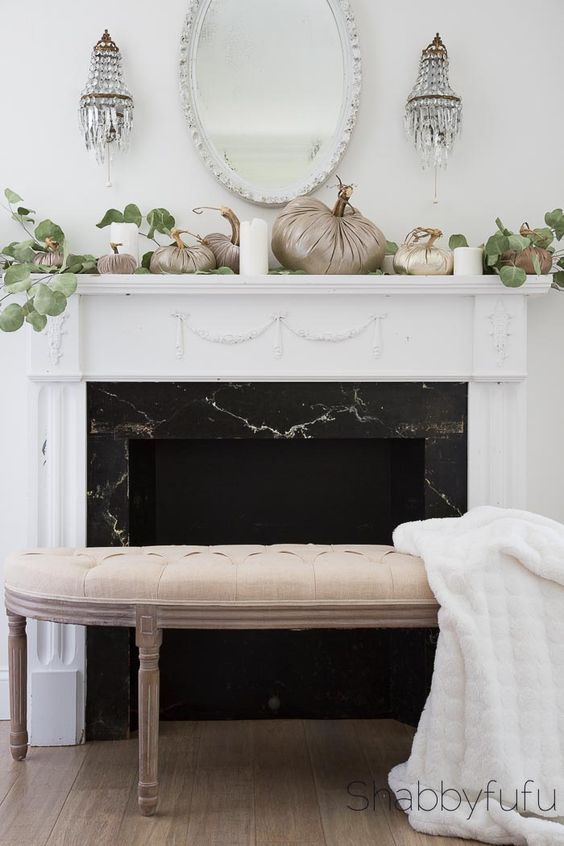 a simple and elegant fall mantel with fabric pumpkins, eucalyptus, candles and crystal lamps over the mantel
