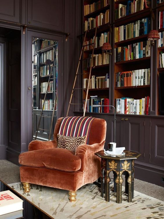 a sophisticated rust velvet chair with gilded legs to create an elegant reading space