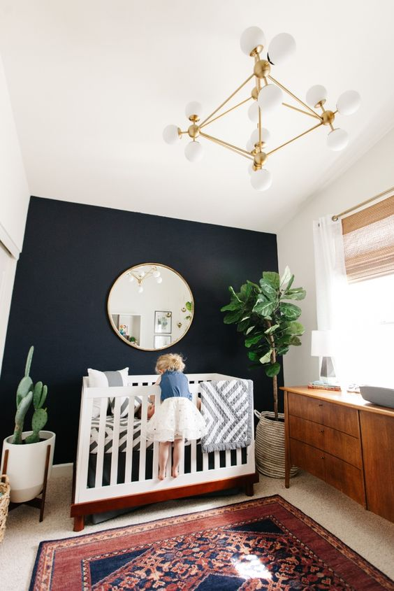 a boho chic nursery with a black accent wall for more drama and a contrast