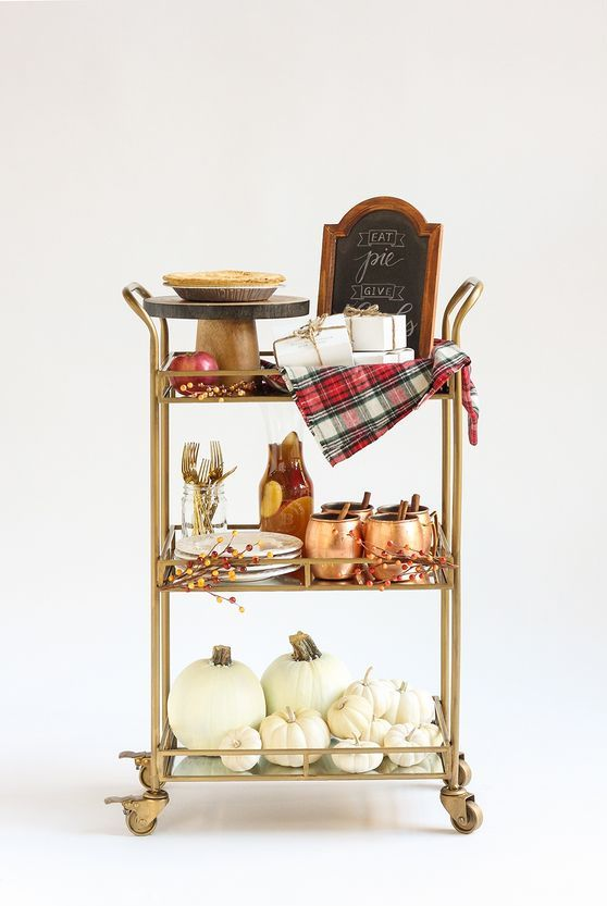 a gorgeous fall bar cart with white pumpkins on the lower shelf, plaid blankets and faux berries
