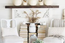 07 a simple mantel with faux white pumpkins and stackes of books placed in front of the non-working fireplace