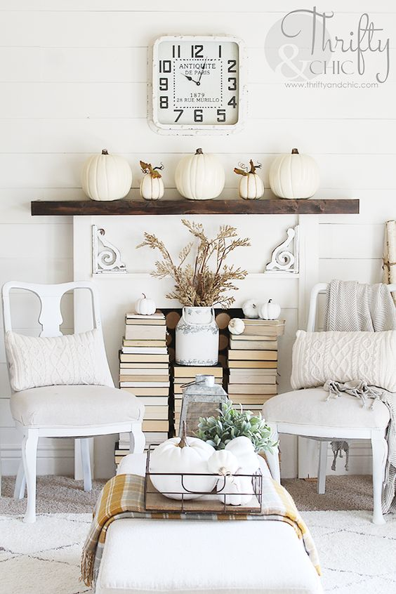 a simple mantel with faux white pumpkins and stackes of books placed in front of the non-working fireplace