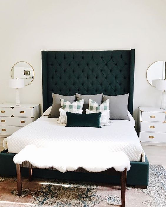 an emerald upholstered bed with a tall statement headboard for a bright bedroom