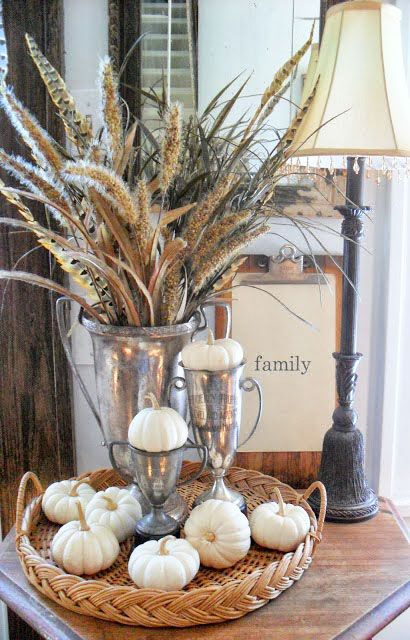 a basket with white pumpkins and a large silver cup with wheat and feathers for a boho feel