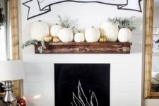 08 faux pumpkins in gold and white pumpkins and pale greenery plus a banner over the mantel