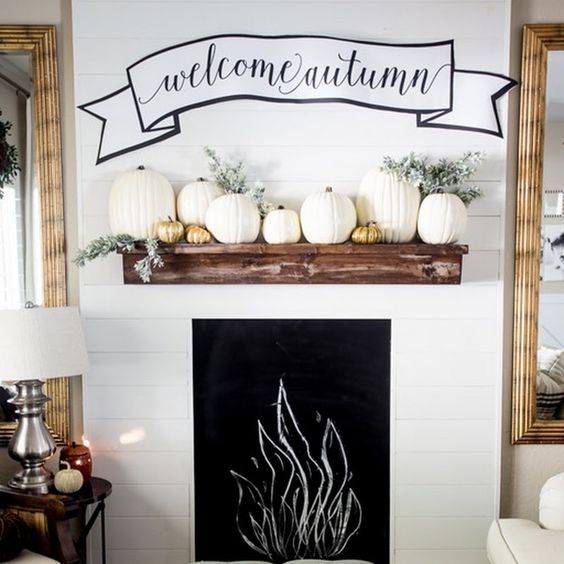faux pumpkins in gold and white pumpkins and pale greenery plus a banner over the mantel