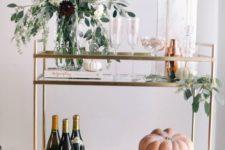 09 a beautiful bar cart with a fall floral arrangement, eucalyptus, white and orange pumpkins
