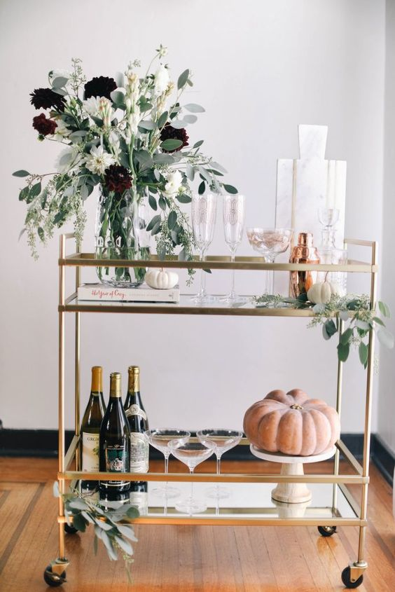 a beautiful bar cart with a fall floral arrangement, eucalyptus, white and orange pumpkins