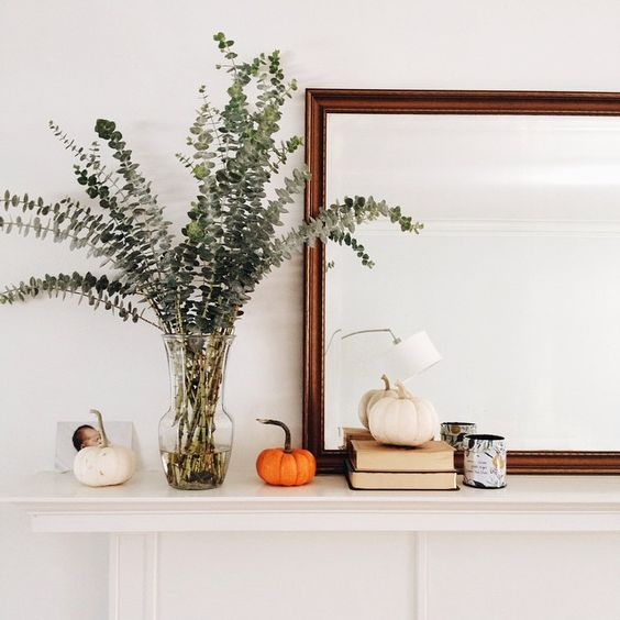 place small faux pumpkins and lush eucalyptus branches in a sheer vase   that's all you need
