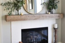 10 a mantel with lush greenery in vases, a large mirror and little pumpkins and a large one next to the fireplace