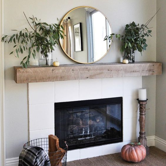 a mantel with lush greenery in vases, a large mirror and little pumpkins and a large one next to the fireplace
