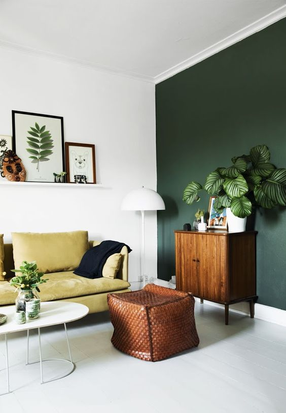 a mustard leather couch contrasts a dark green wall and a brown ottoman creating a bold statement