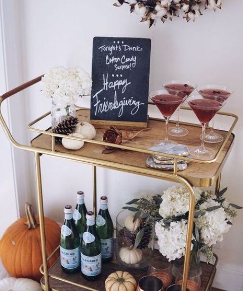 a fall bar cart with faux pumpkins, white flower arrangements and pinecones plus chalkboards