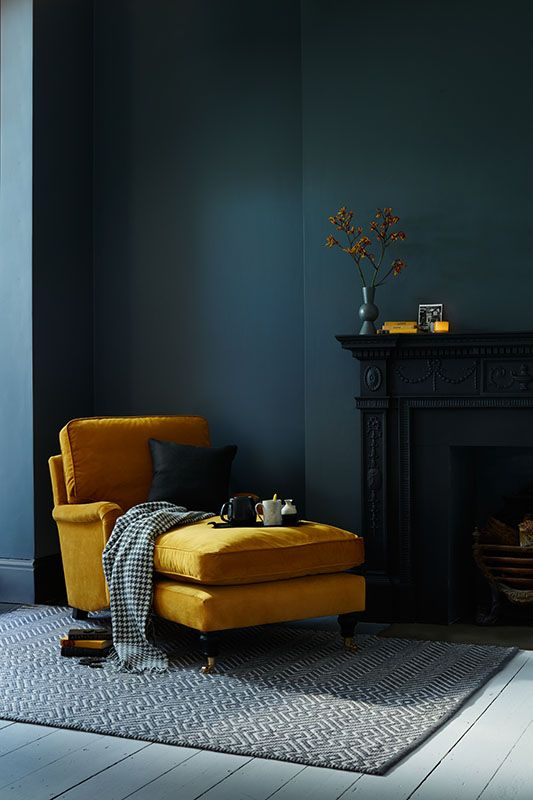 a mustard lounger stands out in front of a dark green wall and brings color to the space