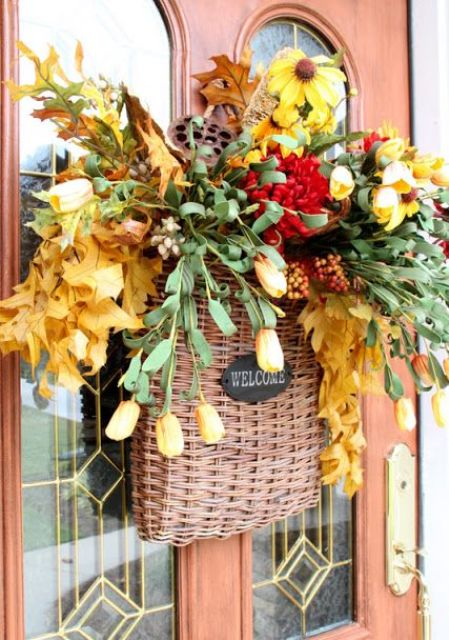 a basket with fall leaves, berries, bloos, greenery and flowers is a great door decoration instead of a wreath