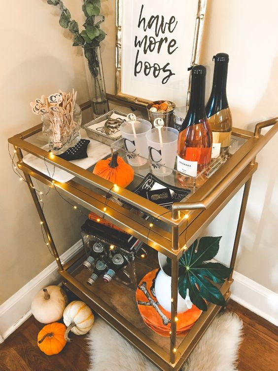 a fall bar cart with orange pumpkins, LEDs abd eucalyptus in a sheer vase for a modern feel